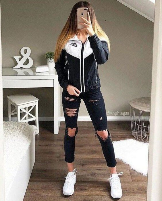 Girl wearing ripped jeans with white tennis shoes and a white jacket with black