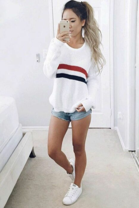 Girl wearing shorts with a big white sweater