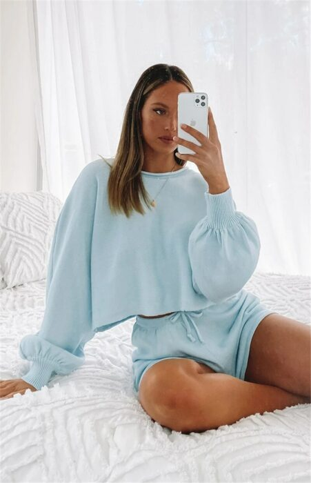 Chica usando uno traje de short con sudadera de manga larga mientras se está tomando una selfie