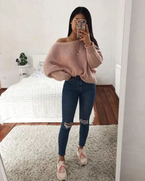 Girl wearing jeans, big pink sweater and white tennis shoes
