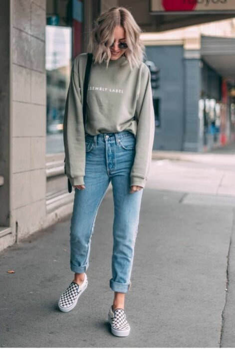 Girl wearing jeans, tennis shoes and a long-sleeved blouse in green