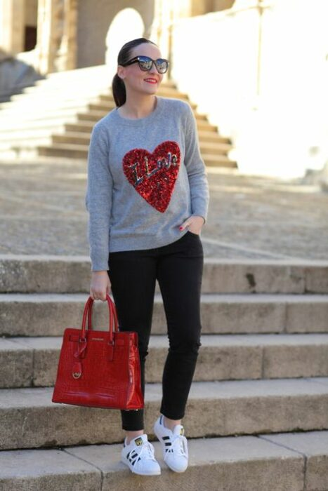 Girl wearing black jeans with gray sweater and red handbag