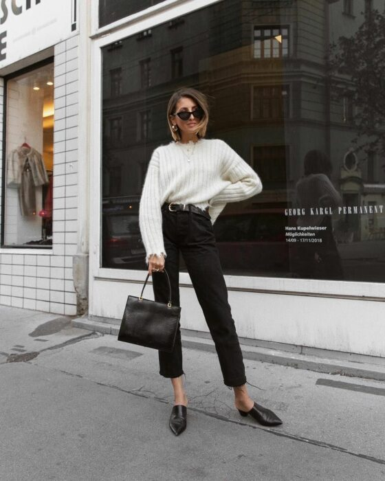 Girl wearing black jeans with a white sweater and flats