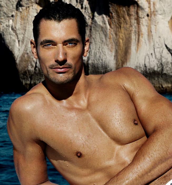 David Gandy, modelo de cabello oscuro con ojos azules, posando sin camisa en el mar