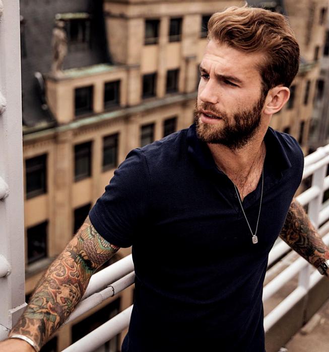 André Hamman; chico rubio usando una camiseta azul marino, con tatuajes en los brazos