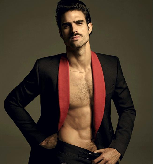 Juan Betancourt; chico de cabello castaño con bigote usando un blazer negro de solapas rojas y pantalón de vestir negro