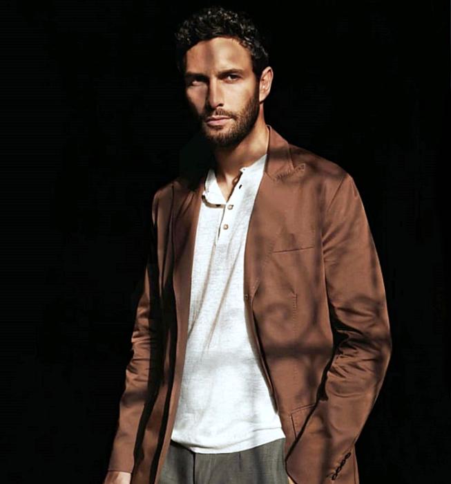 Noah Mills; chico de cabello castaño usando una camiseta blanca con botones en el cuello, blazer café largo y pantalón de vestir café oscuro