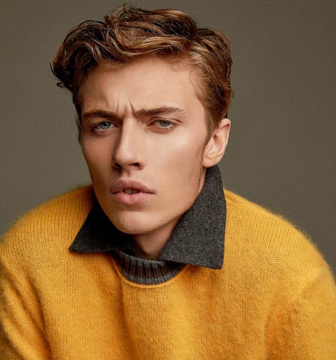 Lucky Blue Smith; chico rubio de ojos azules con una camisa de vestir gris, un suéter amarillo intenso