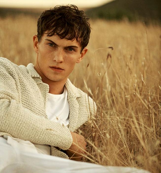 Luc Defont-Saviard; chico de cabello castaño usando una camiseta blanca, suéter tejido beige y pantalón de vestir beige