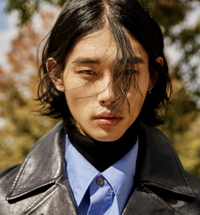 tae min park; chico de cabello castaño usando un top negro de cuello alto, camisa azul de vestir y gabardina gruesa de cuero