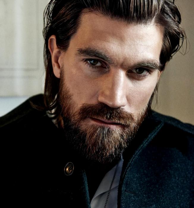 Henrik Fallenius; modelo de barba castaña con cabello largo, usando un abrigo negro