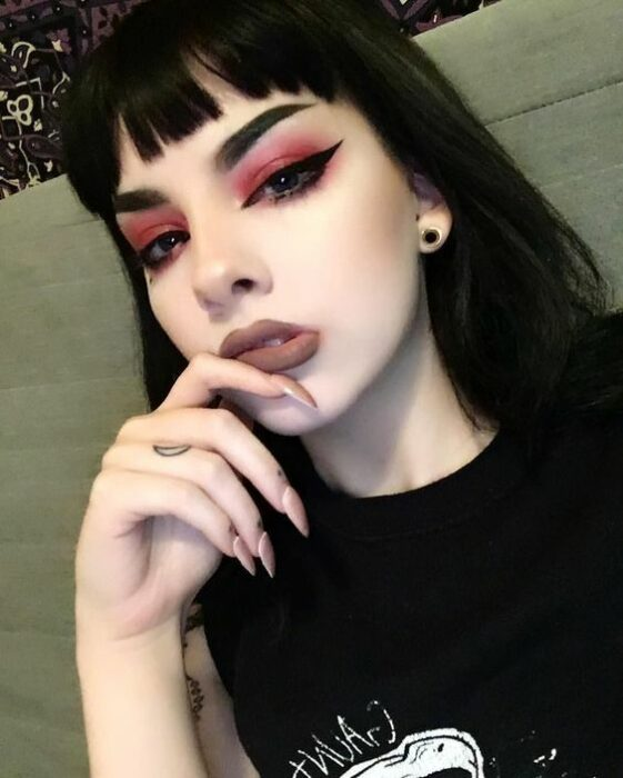 White-skinned girl with black hair and fringes with nude lipstick and smokey eye in red with intense black outlines