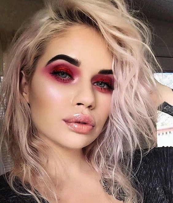 Blonde girl with short curly hair with gloss and smokey eye with red shadow