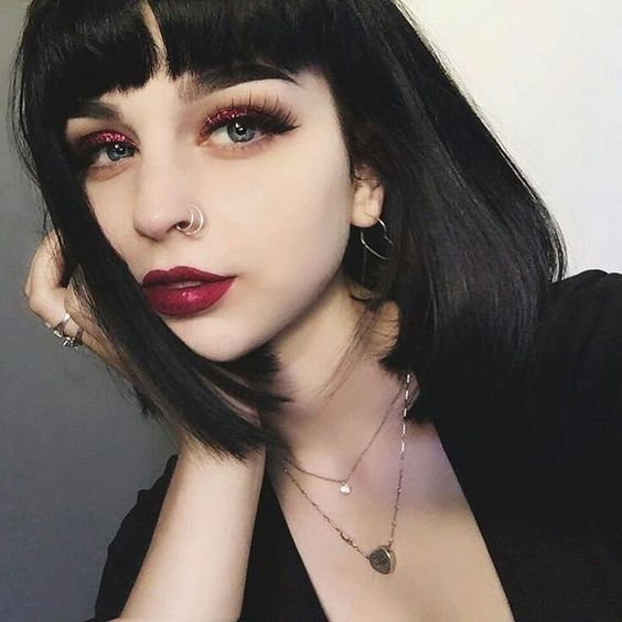 Light skinned girl with short black hair with fringe and red lipstick and red bright shades