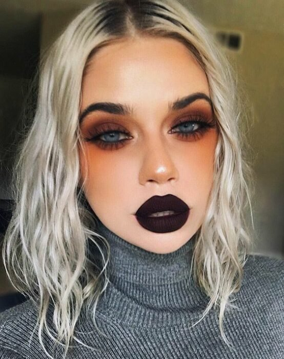 Platinum hair blonde girl with dark lipstick and orange eyeshadows with coffee