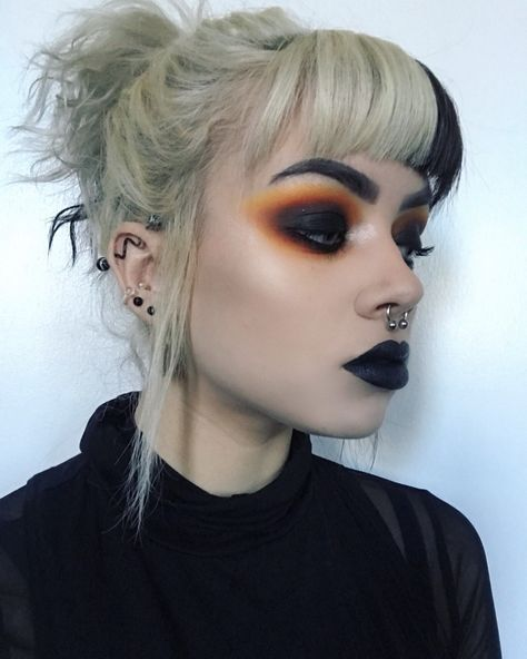 Blonde girl with high ponytail and bicolor fringe with black lipstick and black smokey eye with oranges