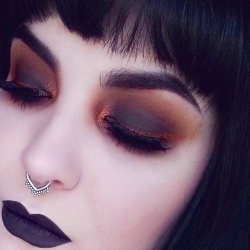 Light skinned girl with dark purple lipstick with black smokey eye with orange and bright brown outline