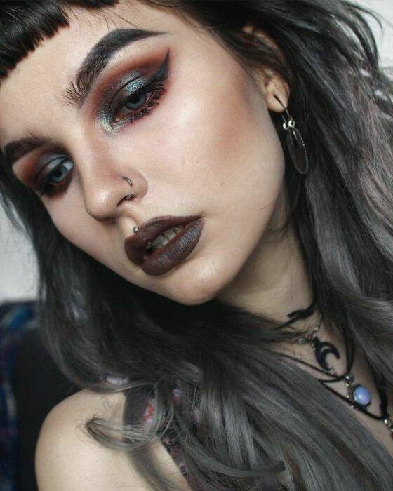 Light-skinned girl with gray lipstick and eyes with green and orange smoky shadows