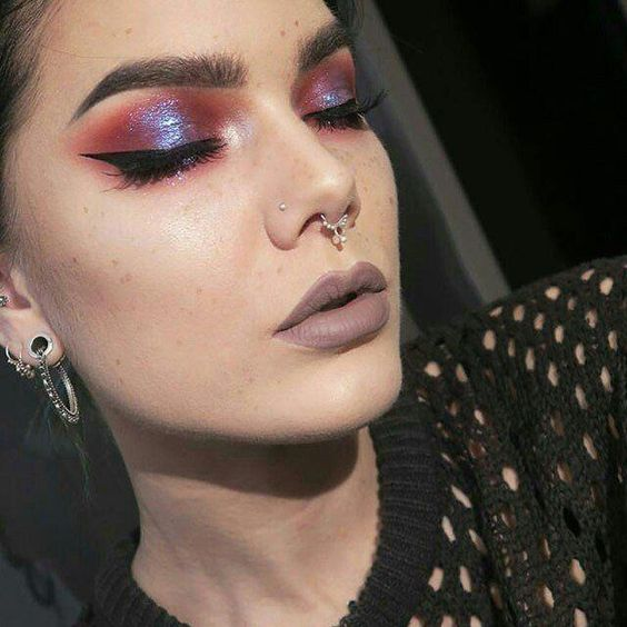 Light skinned girl with gray lipstick and eyes are purple and orange shadows with iridescent effect