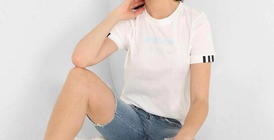 Chica sentada vistiendo shorts, camisa de color blanca