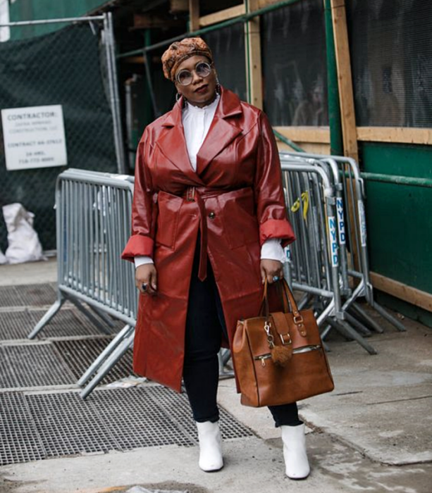 curvy brunette girl wearing sunglasses, a beanie with a coffee print, a white high neck long sleeve blouse, a red leather trench coat, black skinny jeans, white leather ankle boots with a heel and a large brown handbag
