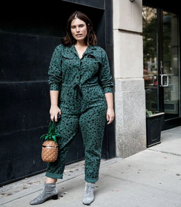 Curvy girl with short brown hair wearing a jumper, green jumpsuit with black polka dots, gray velvet booties with black heels and pineapple-shaped clutch bag