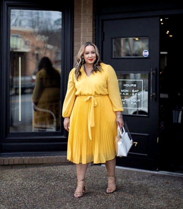 chica curvy de cabello castaño claro usando un vestido amarillo de manga larga, con ajuste en la cintura y falda larga, sandalias de tacón de animal print y bolso de mano blanco