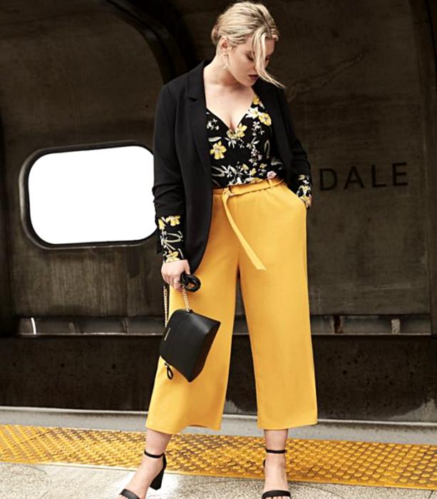 chica rubia usando un top negro de flores, pantalón de vestir amarillo, tacones negros y bolso negro de mano