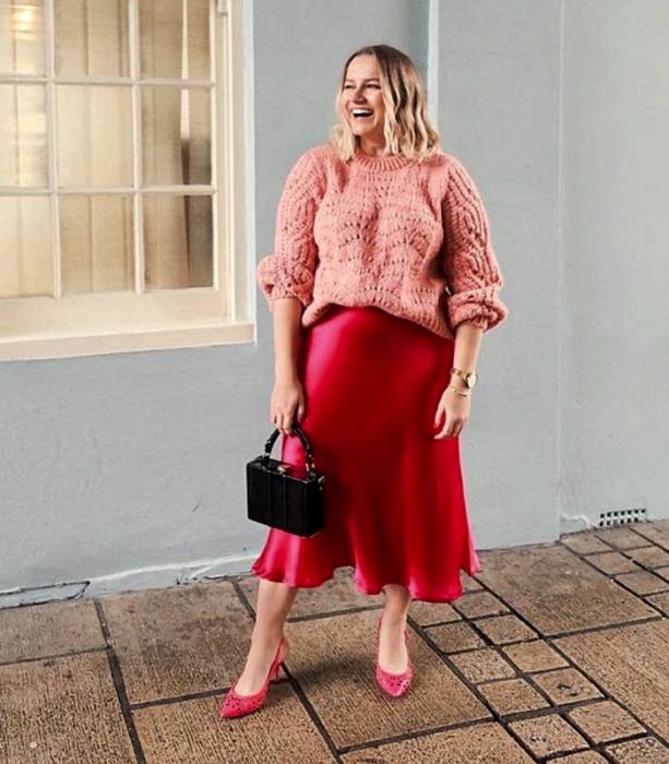 chica rubia curvy usando un suéter oversized rosa, falda de satén rosa fucsia, zapatos de tacón rosas y bolso de mano negro