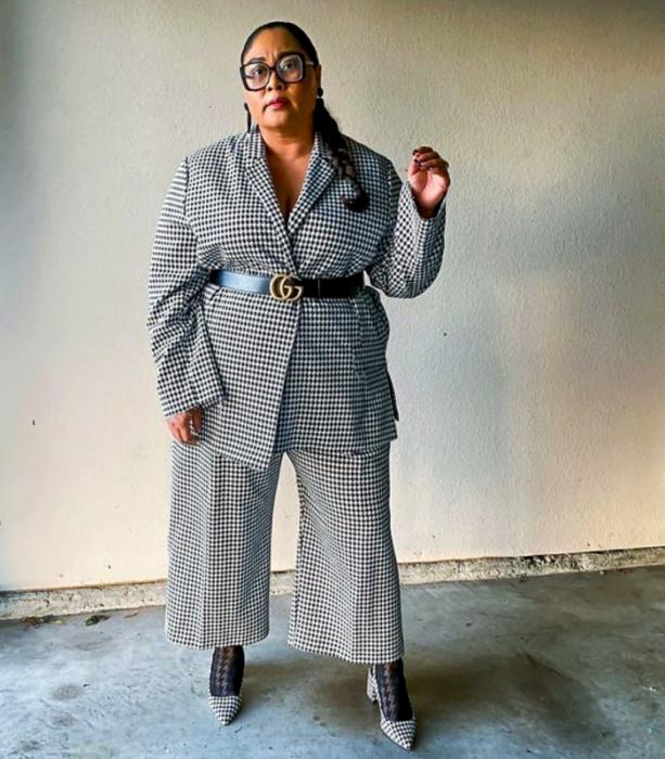 chica curvy morena usando lentes de sol, saco gris de cuadros, cinturón negro, pantalón de vestir gris de cuadros y zapatos de tacón grises