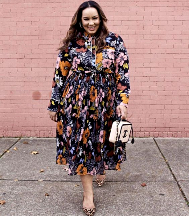 curvy girl with light brown hair wearing a long floral dress with closed neck and long sleeves, beige chanel bag and animal print heels