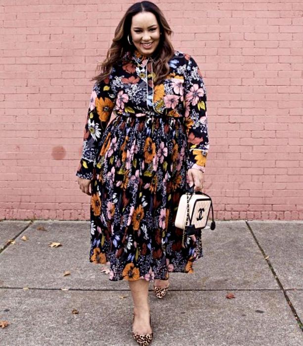 chica curvy de cabello castaño claro usando un vestido largo de flores con cuello cerrado y manga larga, bolso beige chanel y zapatos de tacón con animal print