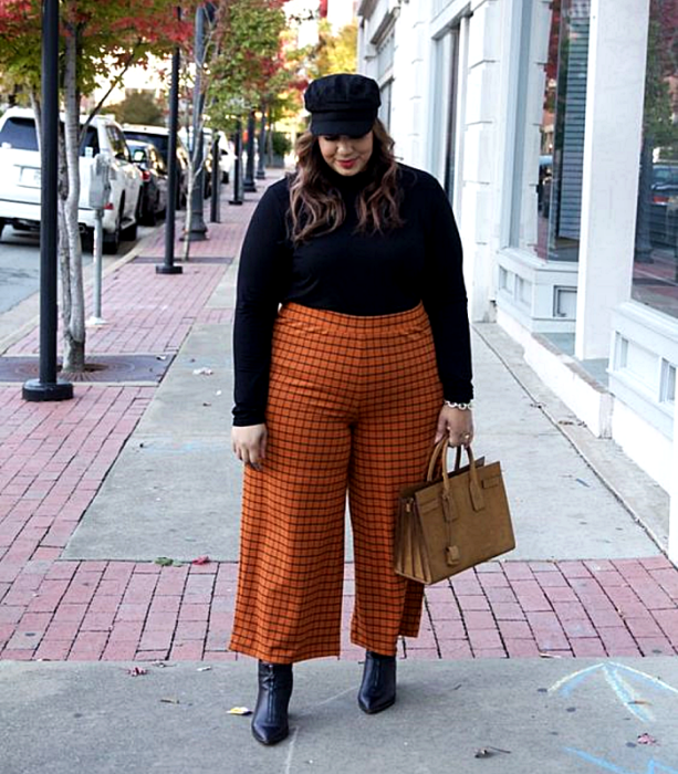 Curvy girl with light brown hair wearing a black beanie, black turtleneck sweater, orange pants with black lines, black leather high-heeled ankle boots and brown tote bag