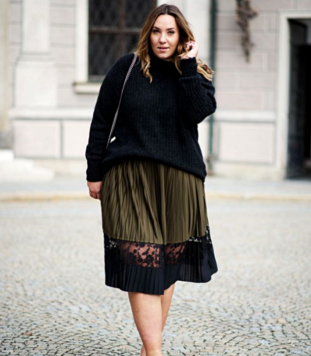 curvy brown haired girl wearing black knitted oversized sweater, long green skirt with black lace, black bag with chain handle
