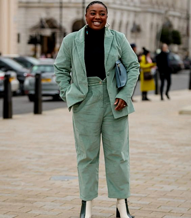 curvy brunette girl wearing black turtleneck sweater, mint green corduroy jacket, mint green corduroy dress pants, beige leather ankle boots with green and sky blue tote bag