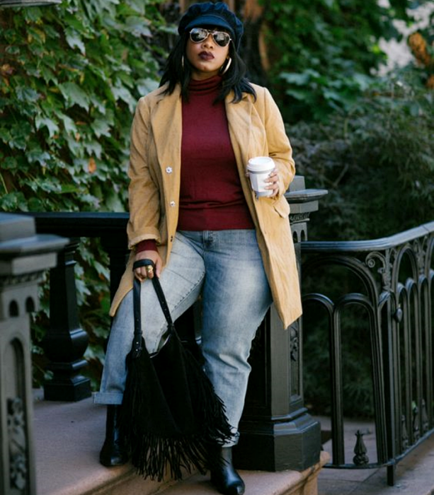 curvy brunette girl wearing a black hat, sunglasses, cherry colored long-sleeved top and high neck, long beige jacket, jeans at the waist, black leather ankle boots, black fringed handbag