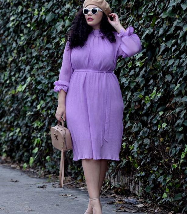 chica curvy de cabello oscuro chino usando un beret beige, lentes de sol blancos, vestido lila de manga larga, bolso beige de mano y sandalias de tacón beige