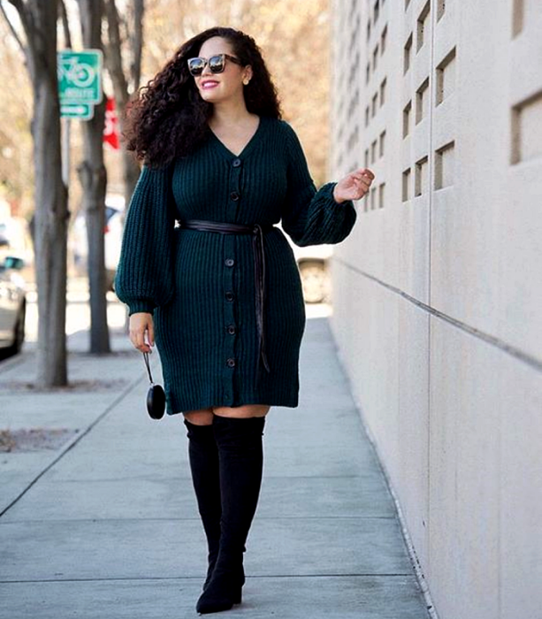 curvy girl with long Chinese hair wearing sunglasses, a navy blue button-knit dress with long sleeves and V-neck, black belt at the waist, long black boots with heels and black mini handbag