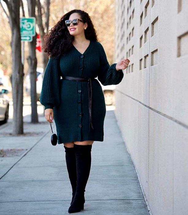 chica curvy de cabello chino largo usando lentes de sol, un vestido tejido de botones color azul marino con manga larga y cuello en V, cinturón negro en la cintura, botas largas negras con tacón y bolso mini negro de mano