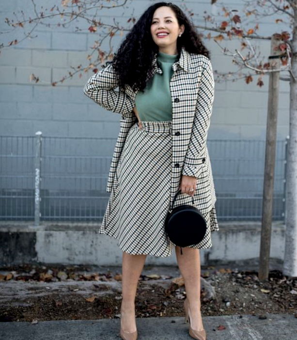 Curvy girl with long Chinese hair wearing a high neck mint blouse, long beige jacket with black lines, long beige waist skirt with black lines, black handbag and beige high heels