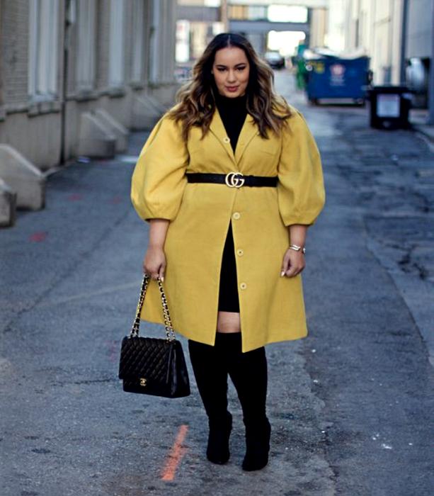 Light haired curvy girl wearing a black high neck top, yellow puff sleeves dress, V neck, black waist belt and black skirt, long high heeled boots and black handbag
