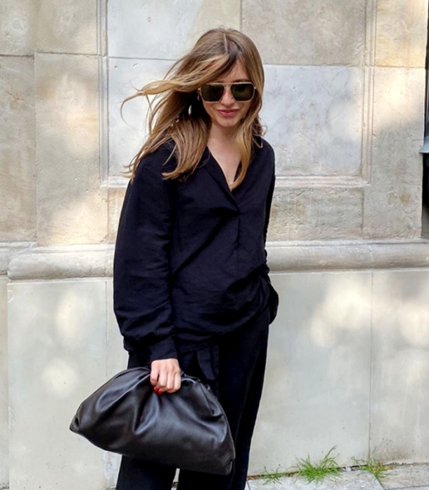 blonde haired girl wearing sunglasses, black oversized shirt, black leather clutch bag, baggy black pants