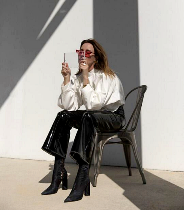 blonde girl wearing pink sunglasses, white oversized shirt, leather pants, black high heel ankle boots