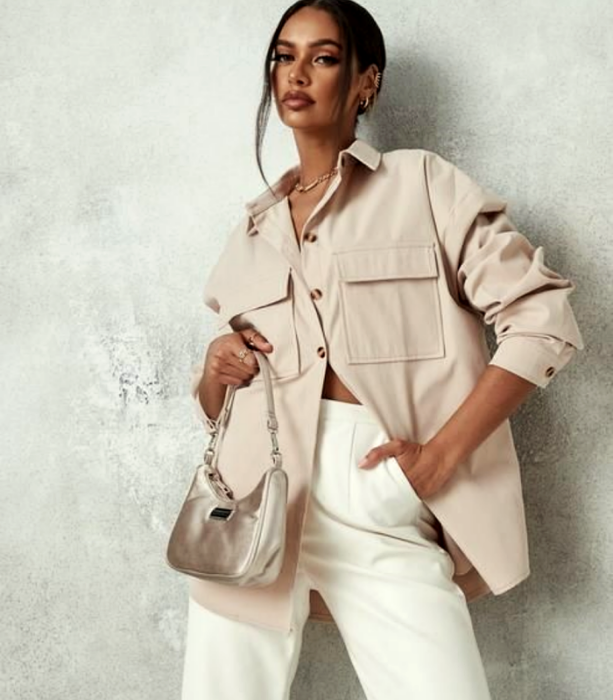 brunette girl wearing a beige oversized shirt with white dress pants at the waist, mini beige guess bag