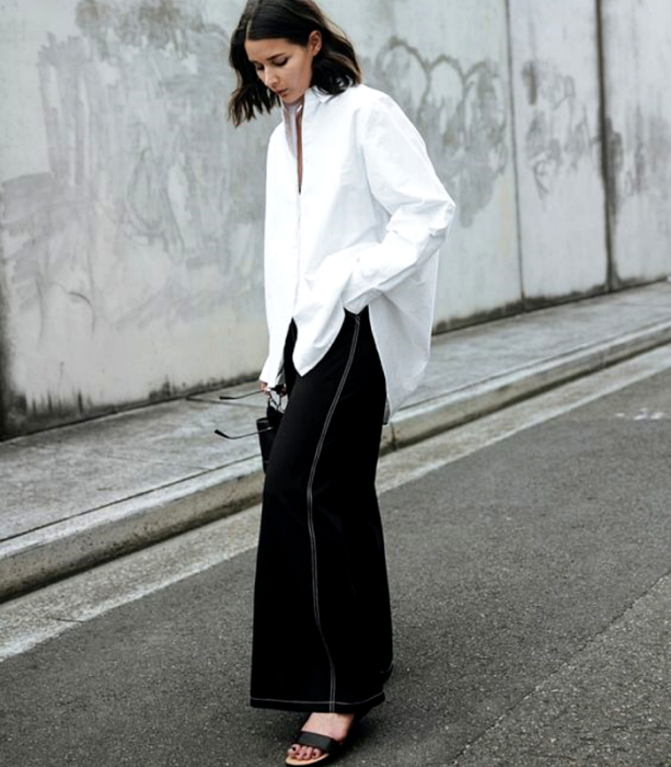 brown haired girl wearing a white oversized shirt, black culottes and black sandals
