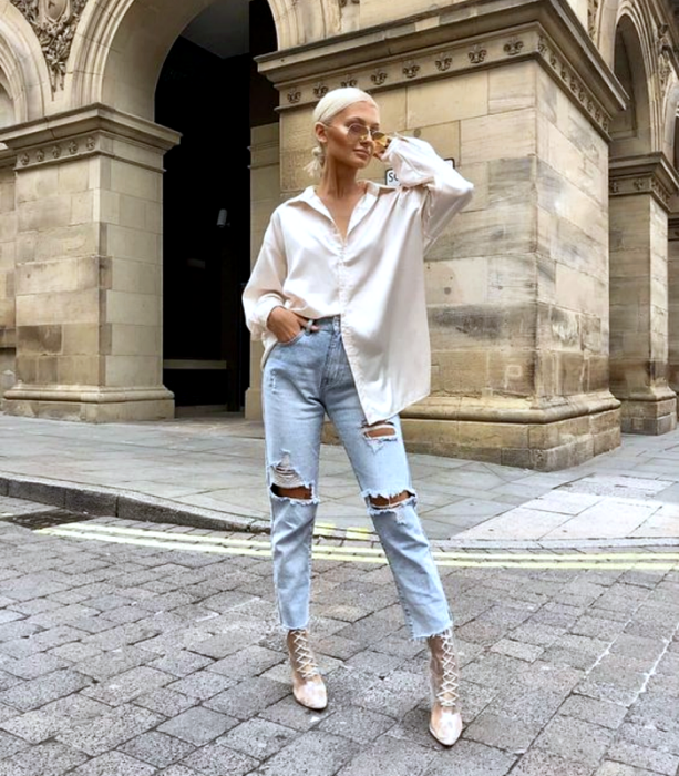 chica rubia usando lentes de sol, camisa oversized blanca, jeans rasgados, botines beige de tacón con agujetas