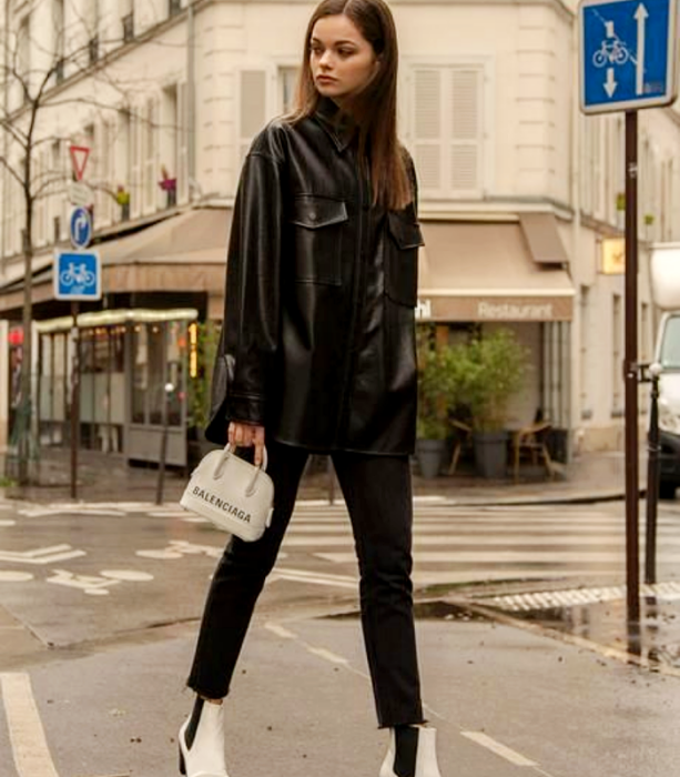 brown haired girl wearing black oversized leather shirt with black skinny jeans, white ankle boots with black views and white mini balenciaga bag