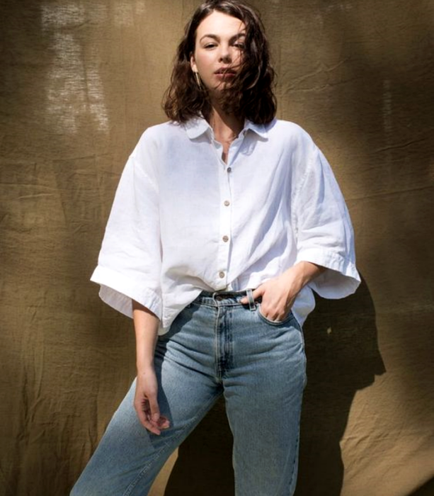 brown haired girl wearing 3/4 sleeve white oversized shirt with waist mom jeans