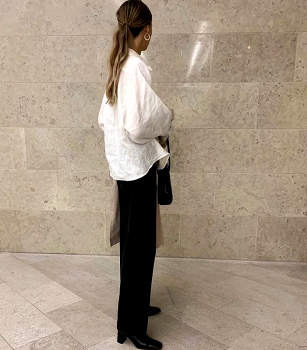 blonde girl in white oversized shirt, black dress pants, black high-heeled ankle boots and black clutch bag