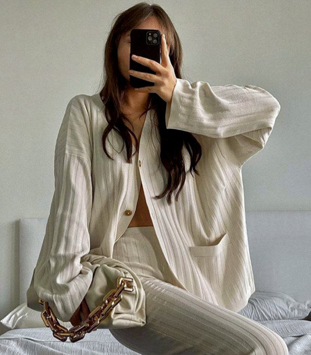 light-haired girl wearing beige knitted white oversized shirt, beige knitted dress pants, and beige handbag with gold chain
